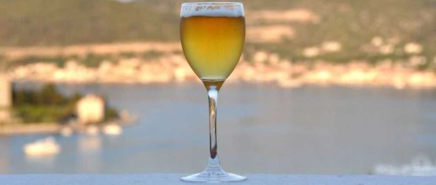 A wine glass full of beer sitting on a balcony railing.